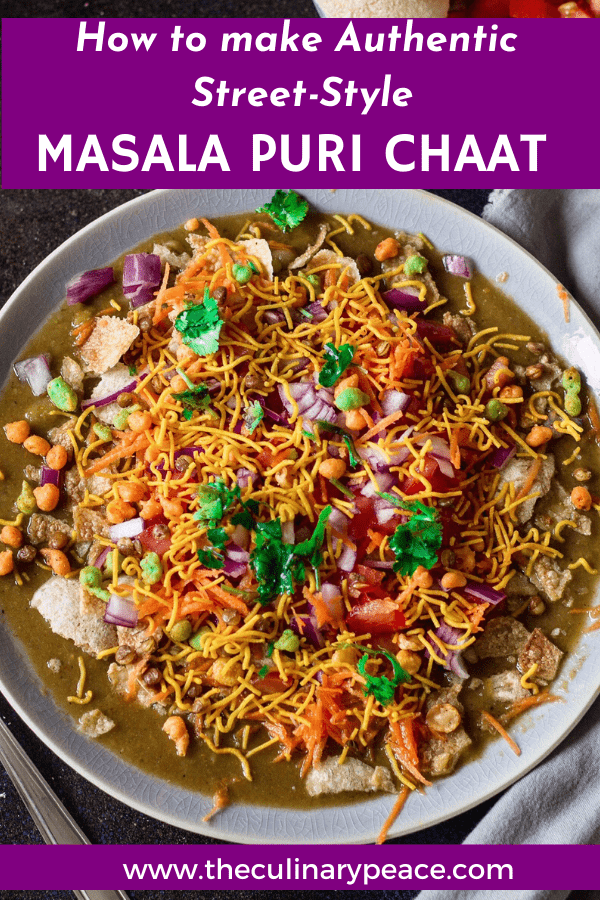 Masala Puri recipe is an the authentic Bangalore style street food served with puris, masala, vegetables like carrot, peas, onions, tomato, coriander leaves and sev served on a grey plate against a dark background. How to make roadside masala puri recipe.