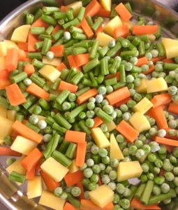 Adding chopped carrots, beans, potatoes and frozen peas to the pressure cooker
