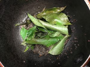 Closeup of curry leaves in a dark bowl