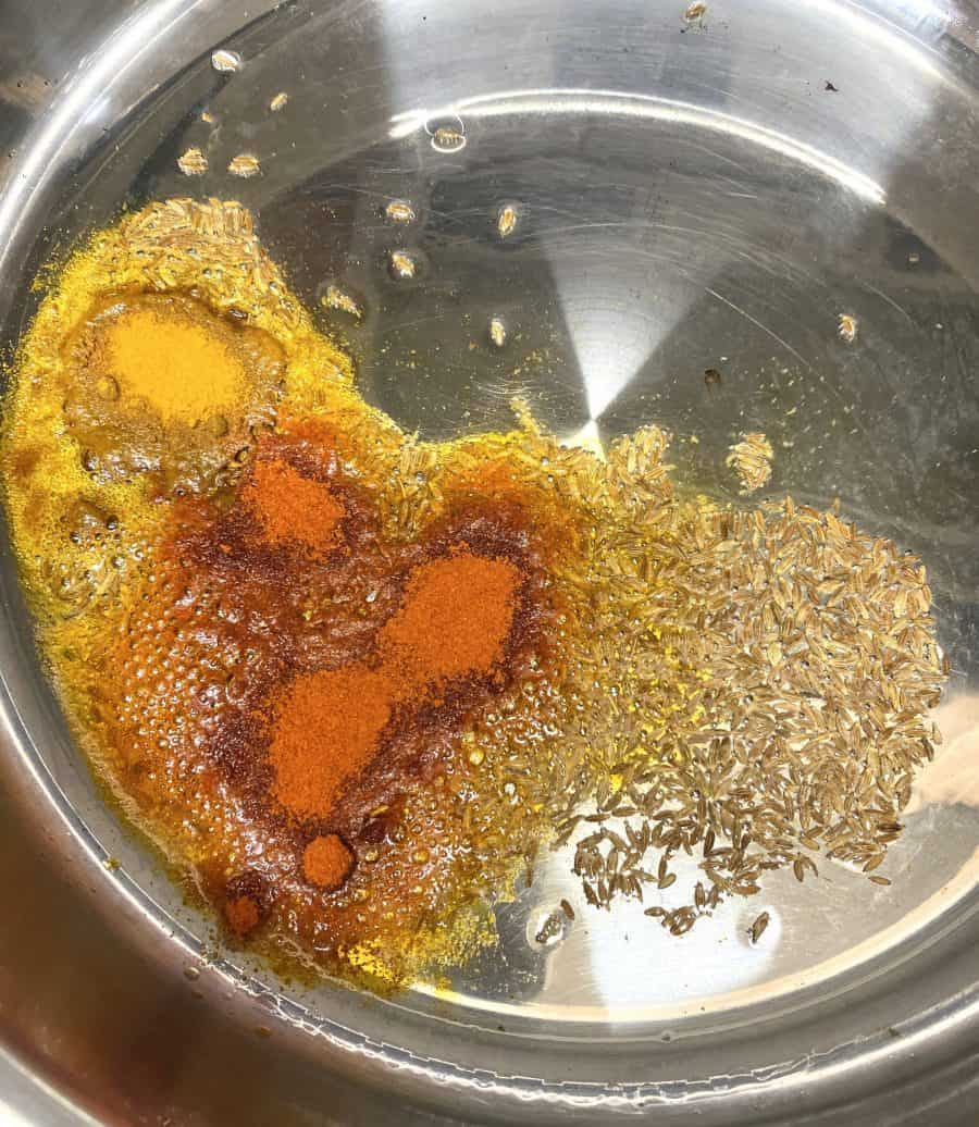 Mixing oil, cumin seeds, turmeric powder and red chili powder together in a pan