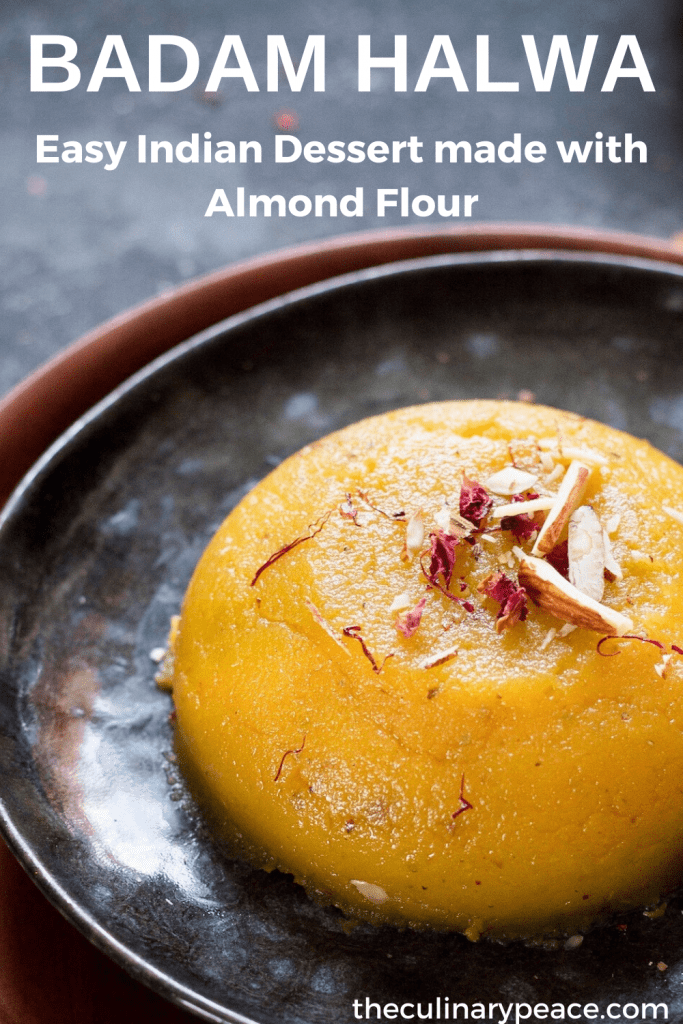 Easy Badam halwa made of almond flour, ghee, sugar, saffron, milk served on a black plate with almond pieces, dried rose petals, saffron strands on top and placed on a wooden plate against a dark background.