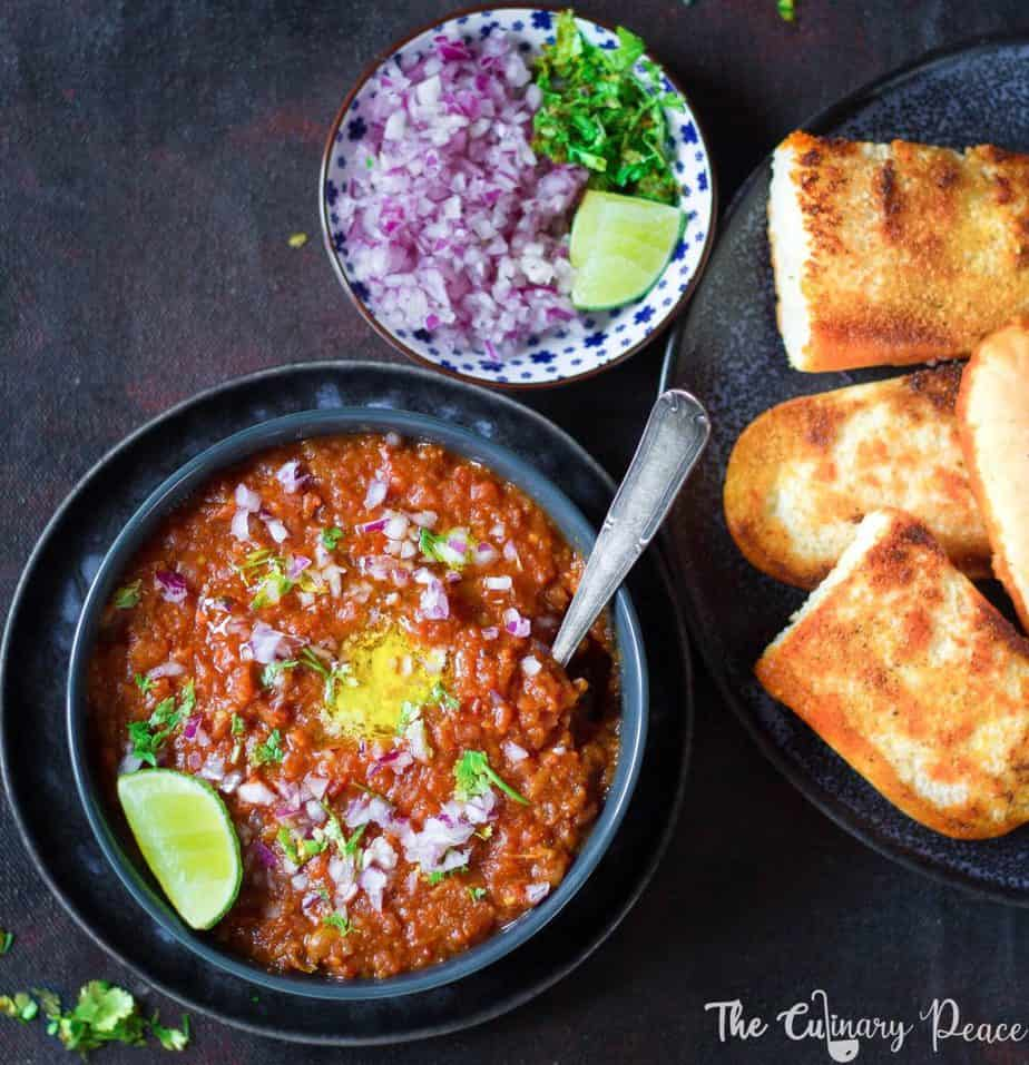Mumbai Style Pav Bhaji Recipe using cooked potato, carrot, beetroot, peas mashed and flavored with pav bhaji masala. Pav Bhaji is served in a bowl with a dollop of butter, chopped onion, cilantro along with dinner rolls.