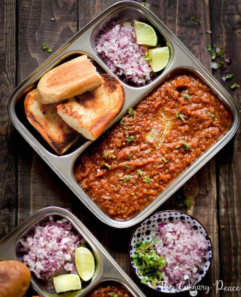 Mumbai Style Pav Bhaji Recipe using cooked potato, carrot, beetroot, peas mashed and flavored with pav bhaji masala. Pav Bhaji is served in a plate with a dollop of butter, chopped onion, cilantro along with dinner rolls.