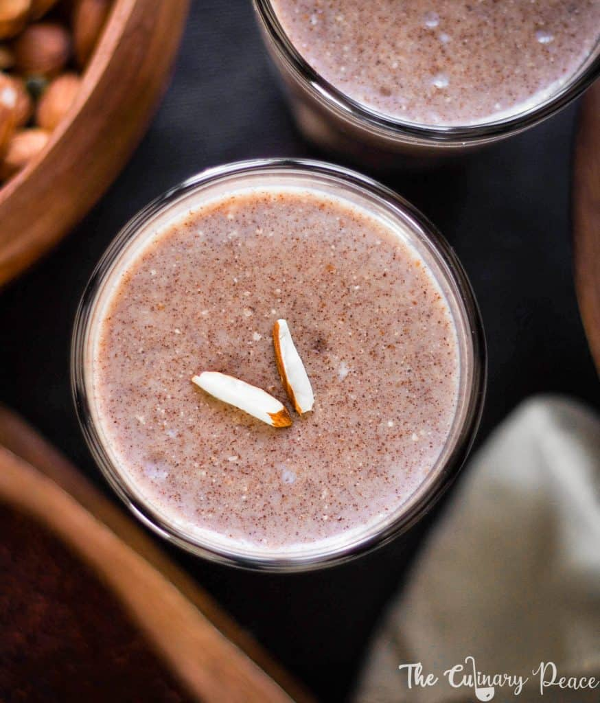 Image of Ragi Malt or Ragi Kanji or Ragi Porridge which is a drink made with ragi flour, milk, jaggery and served in two glasses topped with almonds against a dark background with backlight.