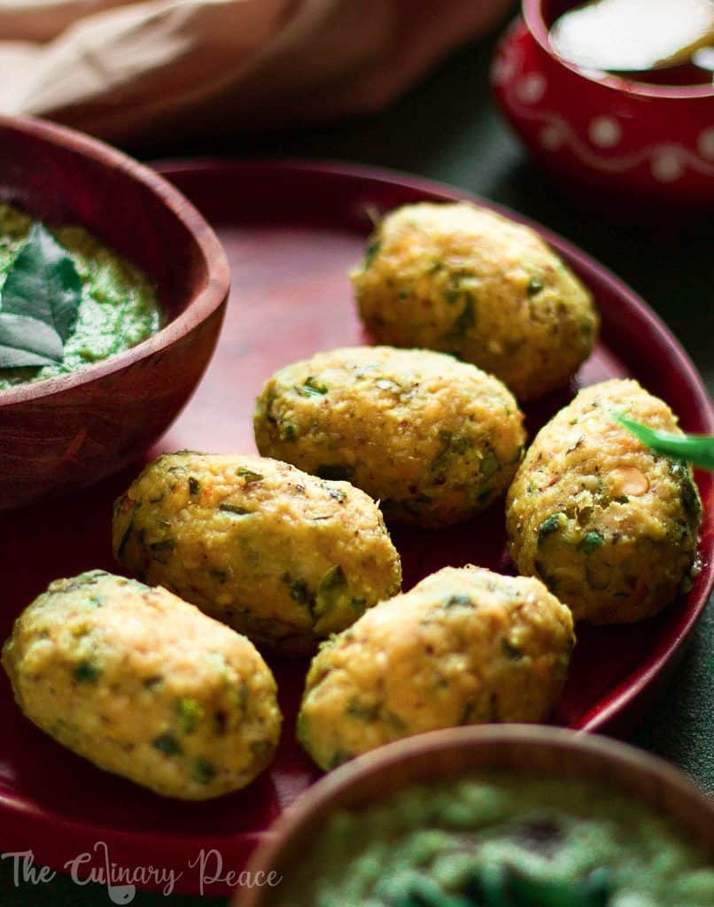 Nuchinunde or steamed lentil dumplings served on a brown wooden plate with a bowl of coriander coconut chutney