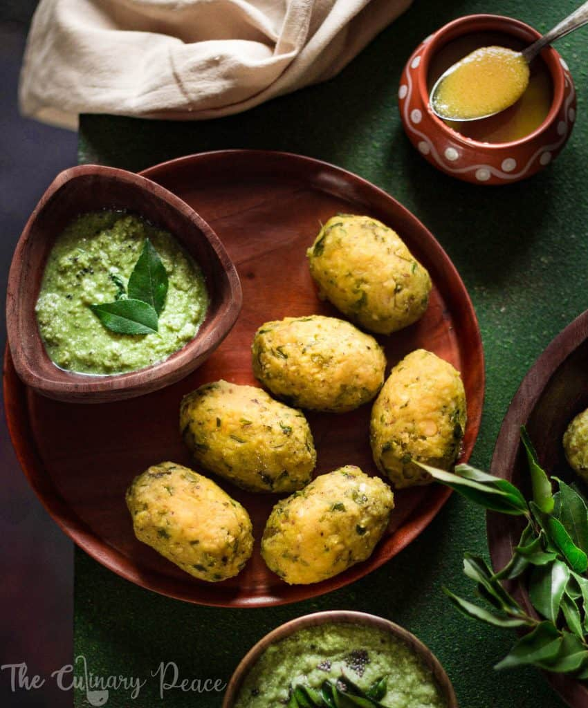 Flatlay of nuchinunde served on a brown wooden plate with a bowl of coriander coconut chutney and ghee on a green background