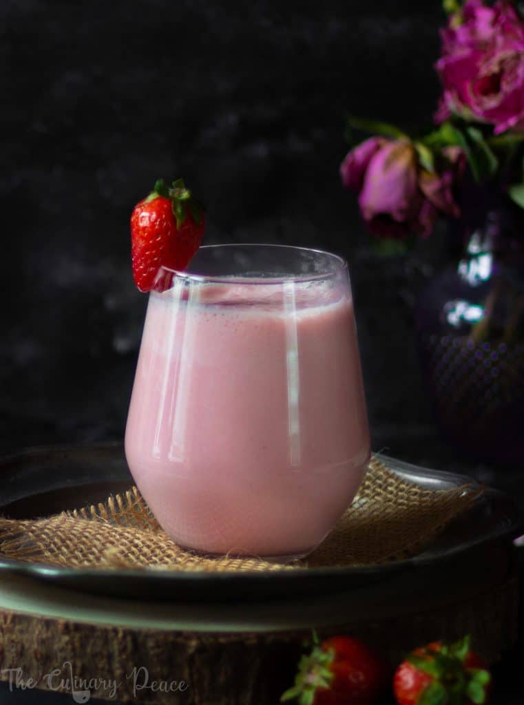 A picture of pink colored strawberry lassi served in a glass with fresh strawberries on a plate against a dark background.