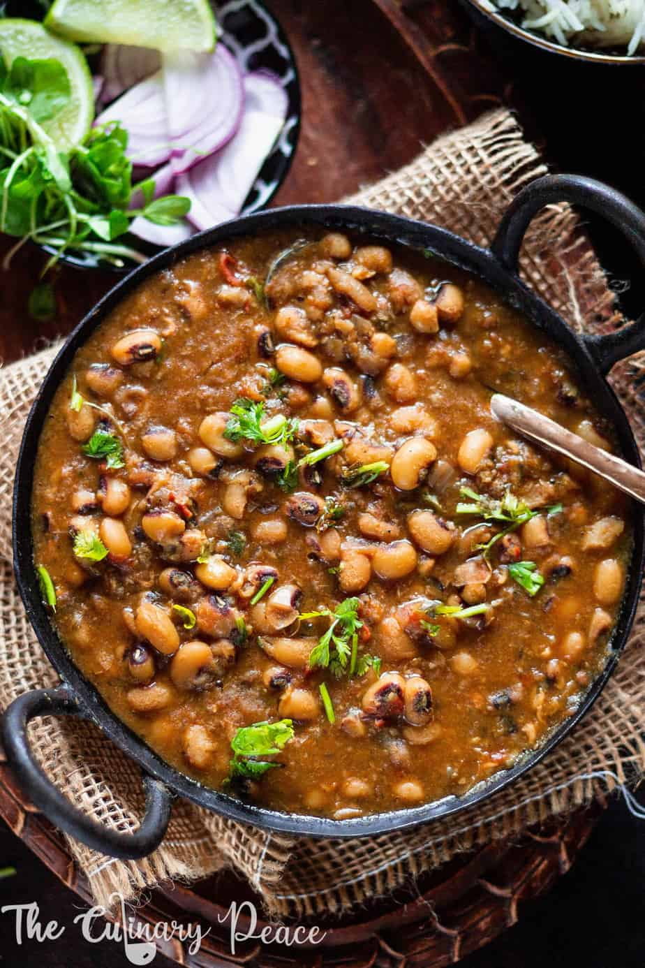 A flatlay image of black eyed peas curry or lobia masala served in a black iron kadai and placed on a wooden plate with onion, lemon and coriander leaves.