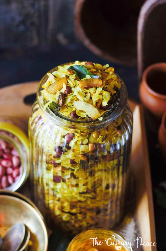 Poha Chivda made of flattened rice, peanuts, roasted gram, raisins, dry coconut and spices stored in a glass jar served on a wooden tray against a dark background.