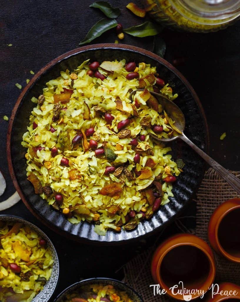 Poha Chivda made of flattened rice, peanuts, roasted gram, raisins, dry coconut and spices served on a black plate with a serving spoon placed against a dark background.