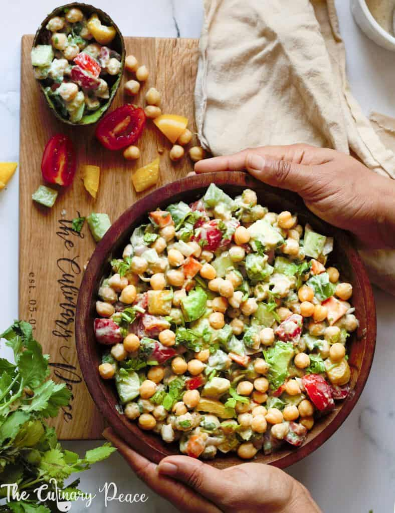 A bowl of vegetarian Indian salad made of chickpeas avocado cucumber tomato salad placed on a white backdrop with yogurt chaat masala dressing.