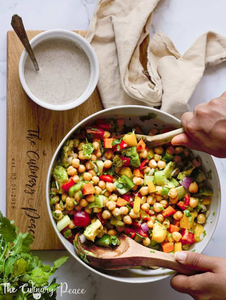 A bowl of vegetarian salad made of chickpeas avocado cucumber tomato salad placed on a white backdrop with yogurt dressing.