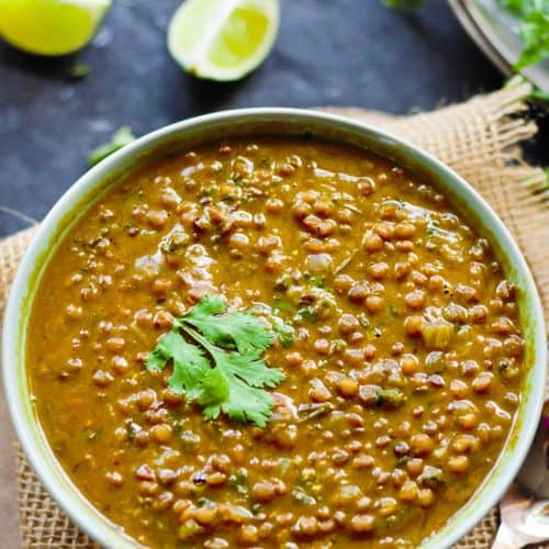 Indian brown lentil curry or whole masoor dal served in a green bowl with cilantro, lemon wedges against a blue background