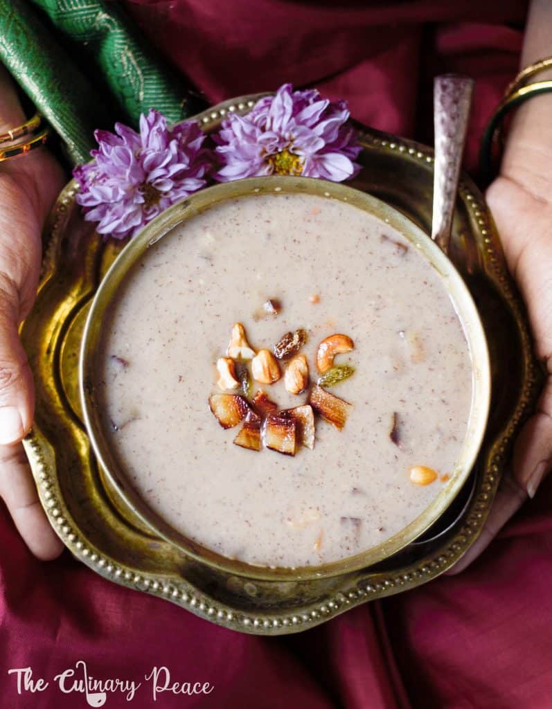 A jackfruit seeds recipe that is jackfruit seeds payasam served in a brass bowl topped with golden fried cashews, dry coconut and raisins, served on a brass plate with flowers against a traditional maroon saree background