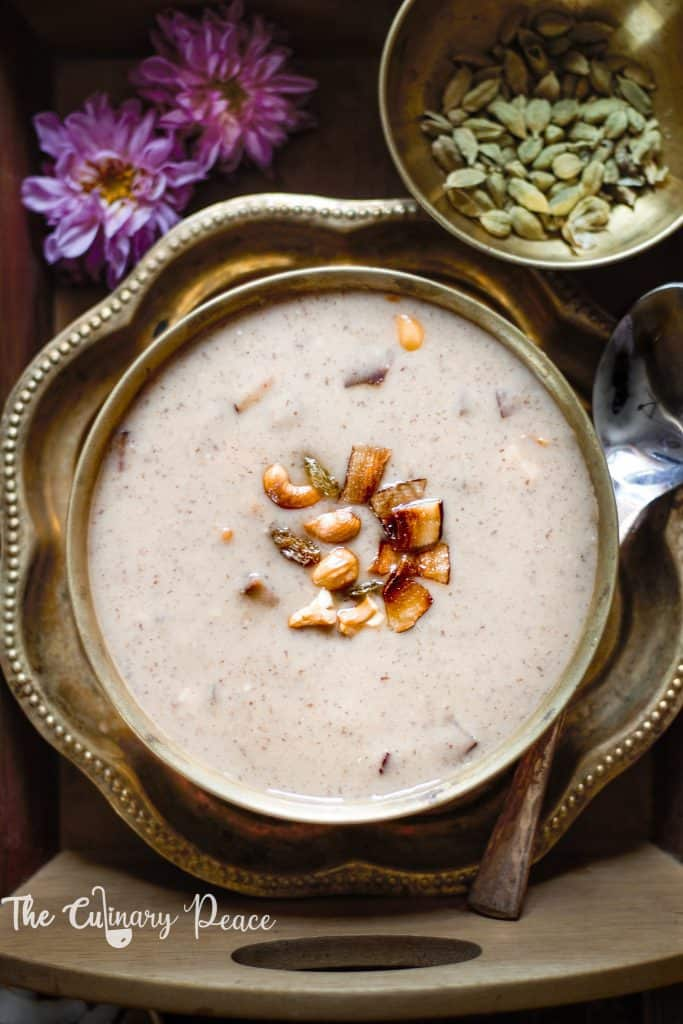 Jackfruit seeds recipe that is jackfruit seeds payasa of slightly pinkish color served in a brass bowl topped with fried brown cashews, dry coconut and raisins placed on a brass antique plate